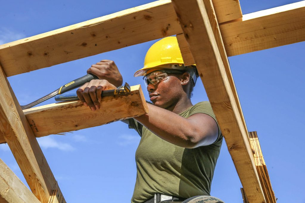 African American woman wearing green shirt and yellow construction hat working with tools on carpentry project.
